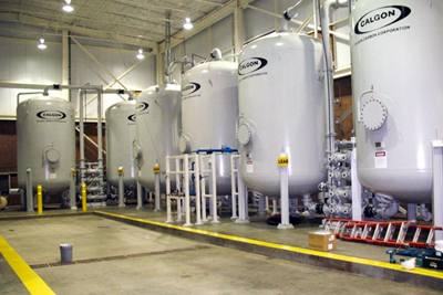 Six large white tanks labelled Calgon stand in a metal building with concrete floors.