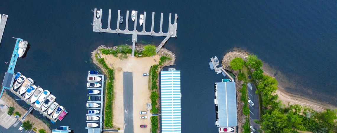 Aerial view of boats slips in a marina on a river.