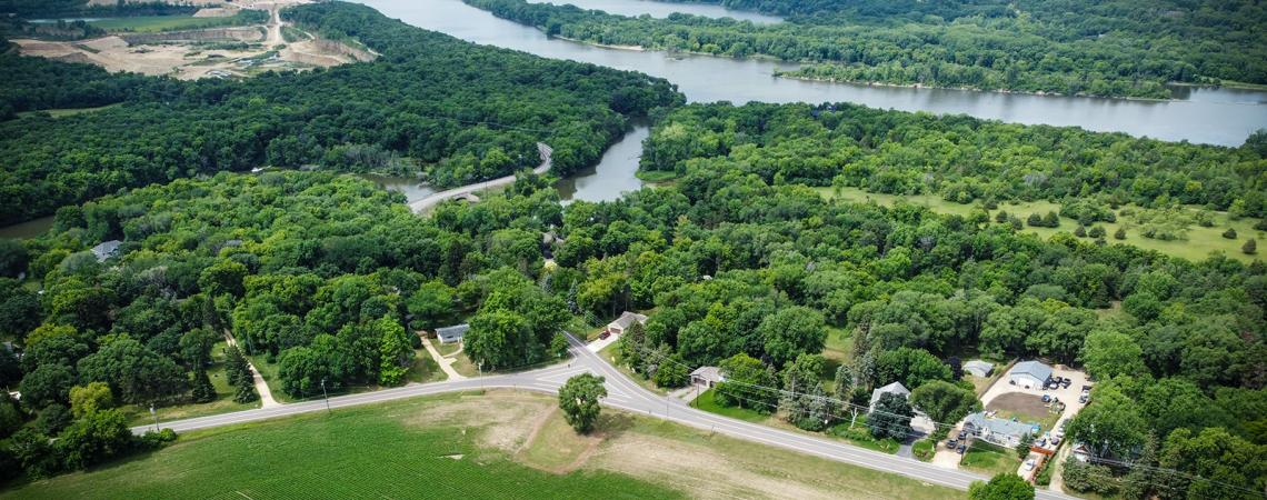 Aerial view of a road running along the edge of a wooded area next to a river.