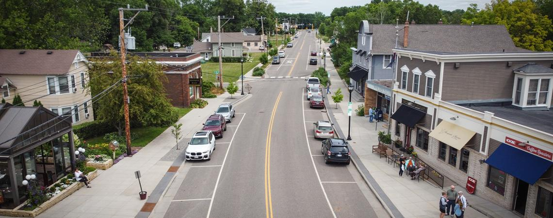 Aerial view of a road running through a small town with businesses and homes on each side of the road and people visiting on the sidewalk.