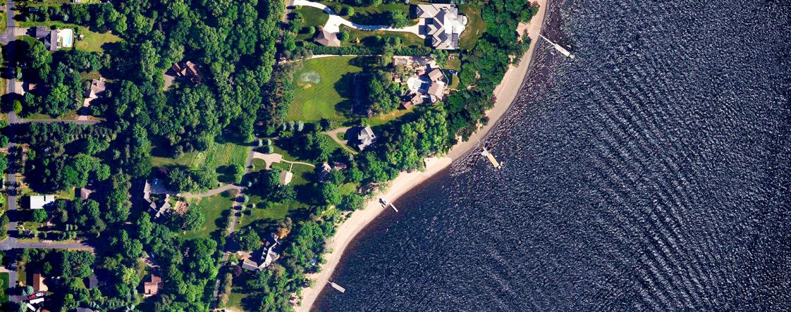 Bird's eye view of a wind rippled river and a tree-lined neighborhood next to it.