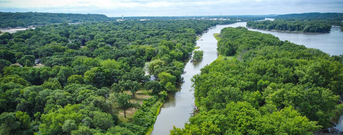 Aerial view of a river running through trees, with a small tree-covered island in the distance.