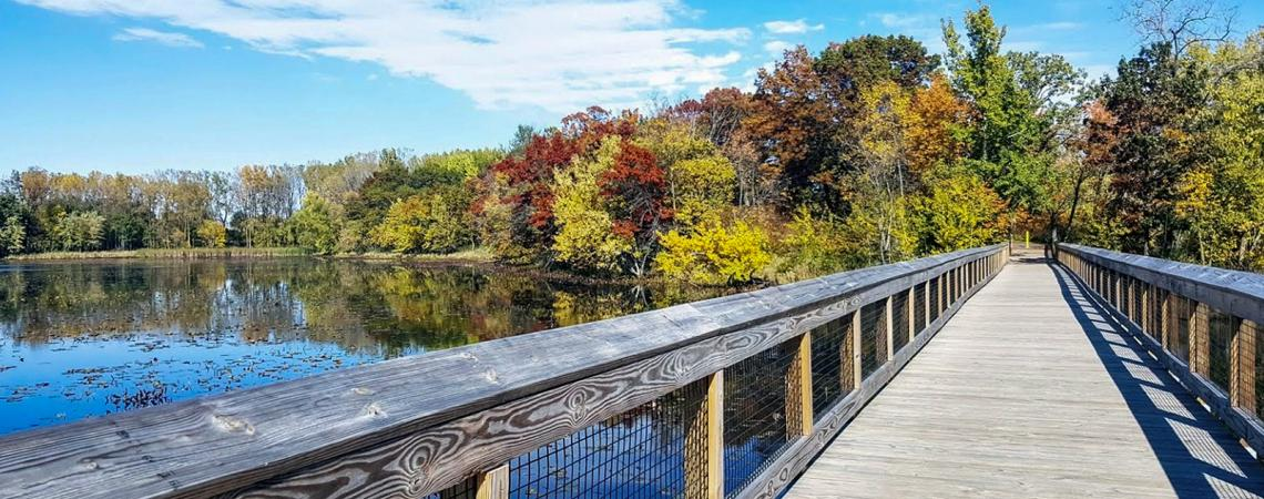 A wooden walkway over a small lake surrounded by red, yellow, and green trees.