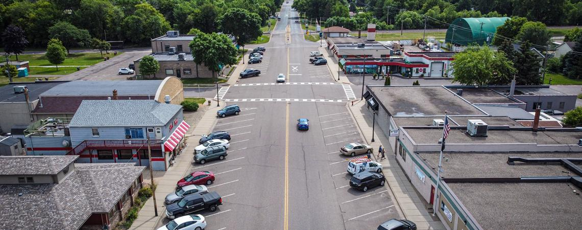 Aerial view of a road running through a small town. Businesses are on each side of the road with cars parked in front of them.