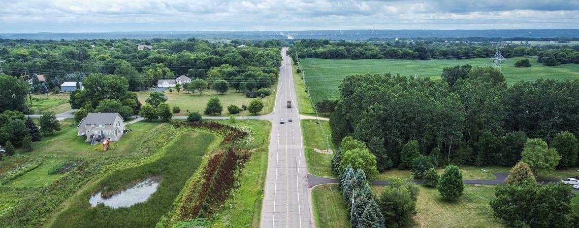 Aerial view of a highway running through a rural area of trees, fields, and homes.