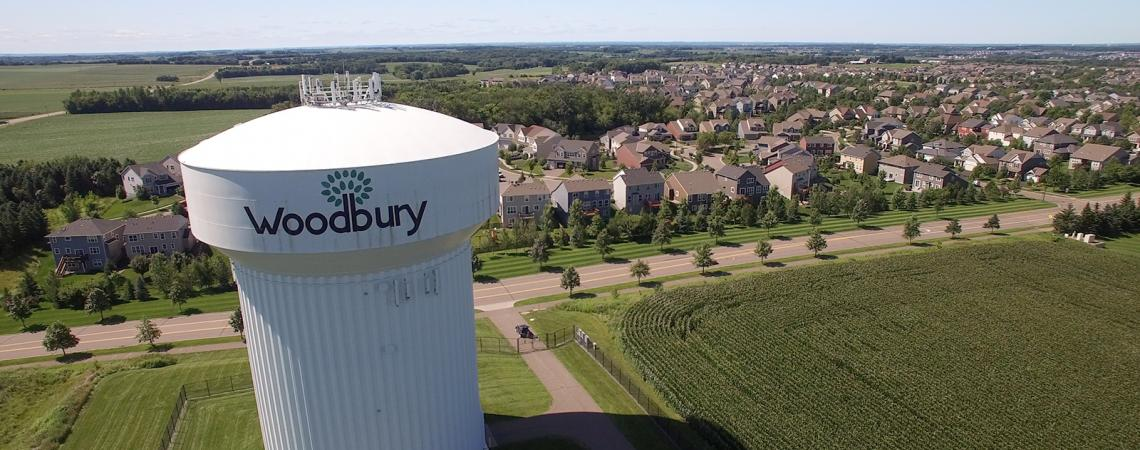 A white water tower labeled Woodbury stands next to a corn field with a suburban neighborhood in the background.